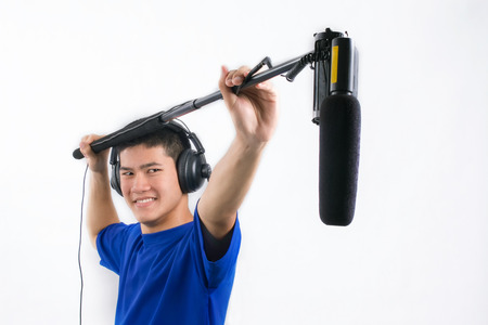 action movie: Man recording movie sound with  boommicrophone on a white background. Stock Photo