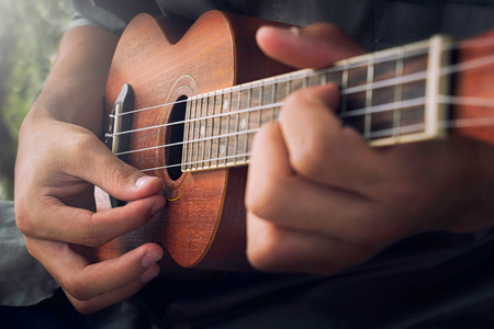 acoustic ukulele: A man playing ukulele in close up view. Stock Photo