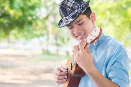 instrumentos de musica: Un hombre que toca el ukelele así la felicidad en parque.