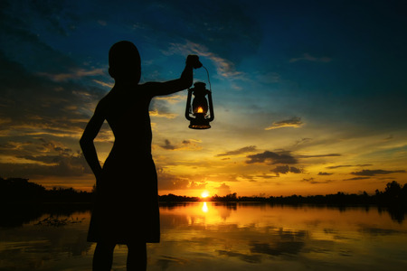 hope: boy holding Lamp looking for sunset . Abstract meaning hope of life.
