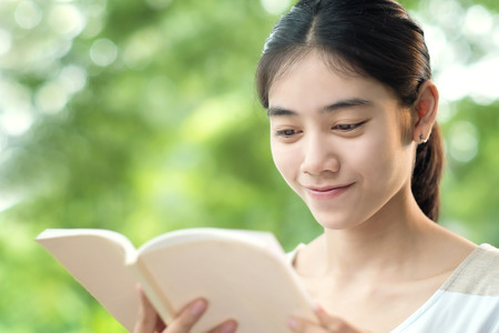 Asian woman reading book in park Stock Photo
