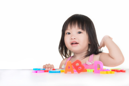 little Asian girl is playing with ABC toy