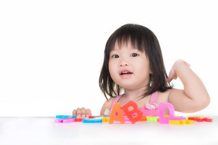 작은 아시아 여자 ABC 장난감으로 재생됩니다.