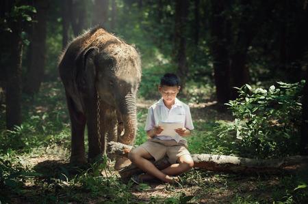 ELEFANTE: Niño leyendo el libro con el elefante en la escuela Aldea del elefante en Tailandia.