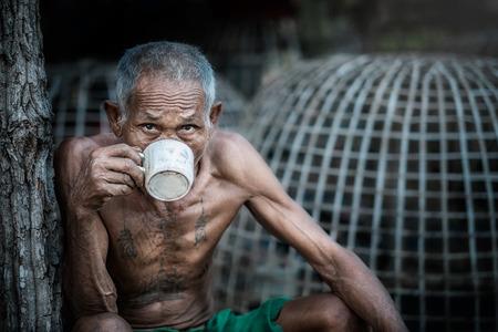 hombre pobre: El viejo para beber caf� relajado en countryside.This es la manera asi�tica vida.Este es f�cil y felicidad. Foto de archivo