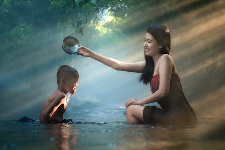familias felices: Hermana y hermano están bañando en un arroyo.