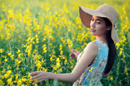 sexy asian woman: Beautiful woman enjoying with flowers on field, holding plant, lady touching nature, aromatherapy concept.