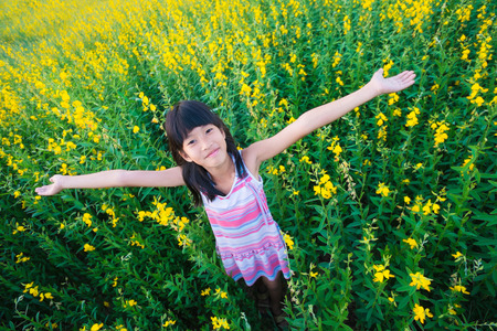 ventilate: girl standing in flowers field with The feeling of freedom. Stock Photo