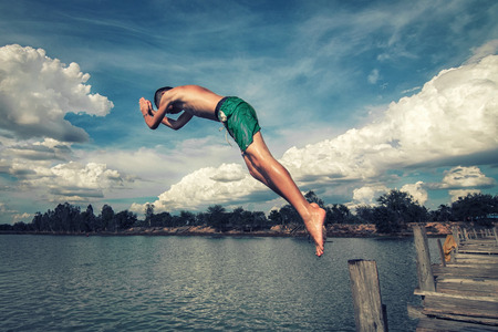 Boy jumps from the bridge into the water