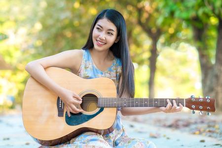 artistas: Mujer que juega a la mujer guitar.Asian tocar la guitarra por el tiempo divertido.