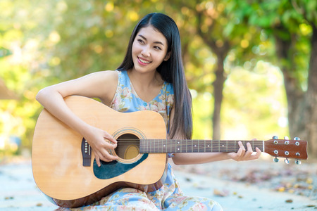 woman dress: Woman playing guitar.Asian woman playing guitar for funny time.