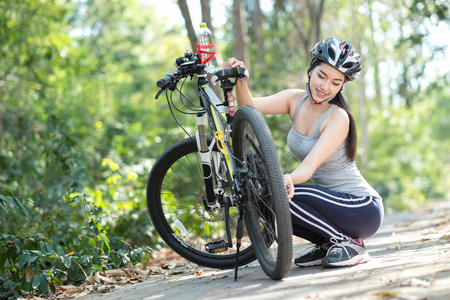 road cycling: Woman repairing bike. Women are troubleshooting while spinning bicycle. Stock Photo
