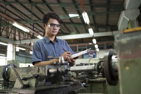 lavoratore prendere atto per il controllo machine.Man il controllo della qualità del lavoro industriale.