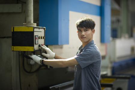 punch press: Man controlling hydraulic Press brake for folding steel. Stock Photo