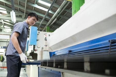 Man het regelen van hydraulische pers machine voor het snijden van staal.