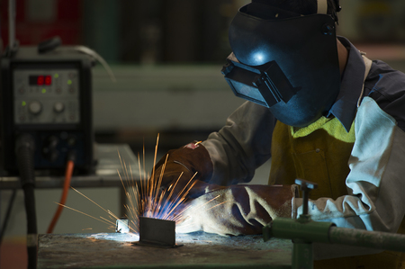 protective clothing: man welding steel by skill.Men wear protective clothing during work.
