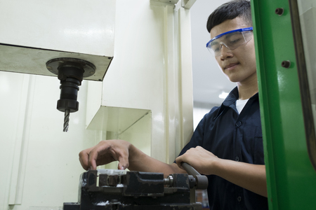 Technician controlling CNC machine.Man input workpiece to machine. Stock Photo
