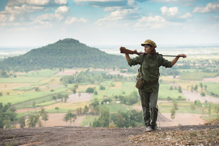 Commissary carrying a gun stands on a mountain. Foto de archivo - 111346029
