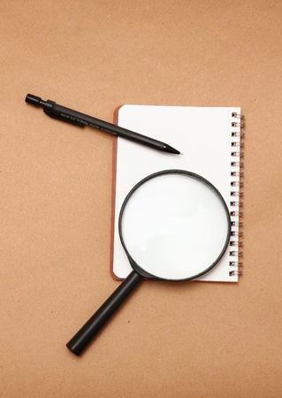 Blank reporters notebook and pencil on a brown paper background,magnifying glass  photo