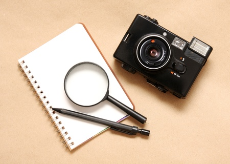 Blank reporters notebook and pencil on a brown paper background,magnifying glass and camera