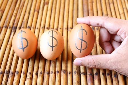tree eggs on the floor.The dollar sign on eggs. Stock Photo