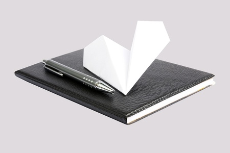 Notebook and pen with paper airplane photo