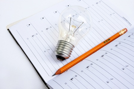 Open notebook with pencil and light bulb. photo