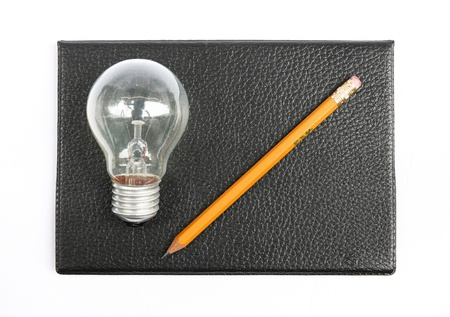 Black notebook with pencil and light bulb. photo