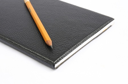 Black notebook with yellow pencil. photo