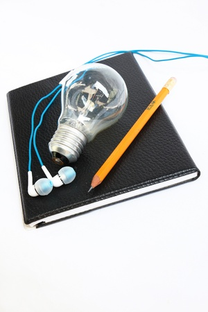 Black notebook with yellow pen cil and light bulb,Earphone photo
