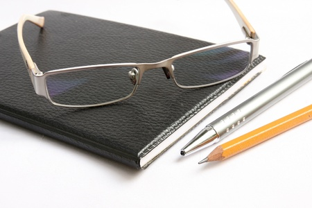Black notebook pen and glasses on white photo