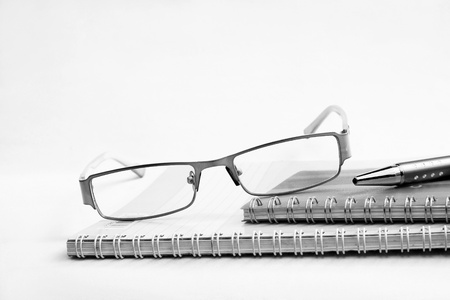 notebook pen and glasses in composition in black and white