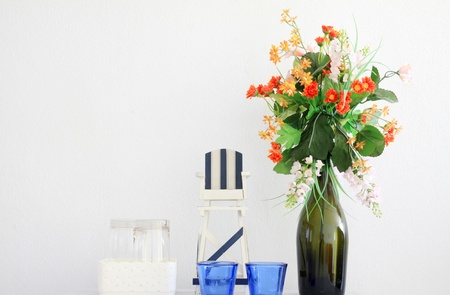 Vase with Plastic flowers and white wall photo