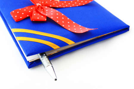 book with ribbon and pen on white Stock Photo - 12834451