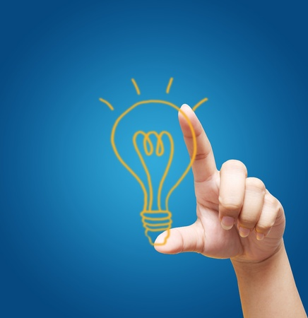 hand holding light bulb on blue background  photo