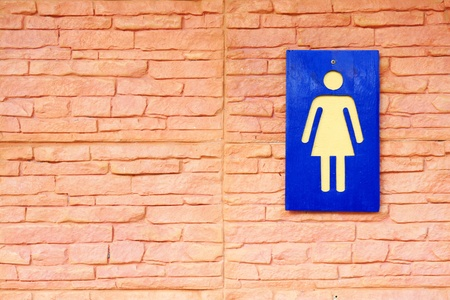 Sign of toilets and brick wall photo