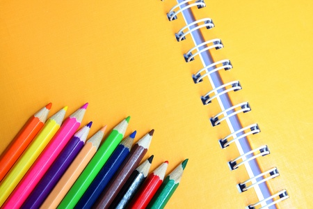 yellow notebook and colour pencils photo