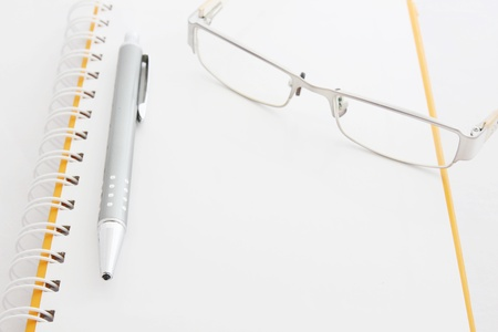notebook glasses and yellow pencil on white  photo