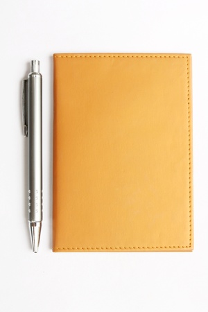 yellow Notebook with pen on white