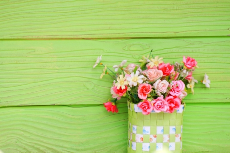 Vase with Plastic flowers and green wall photo