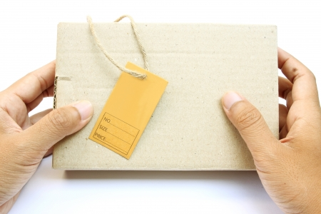 Hand holding a box with brown empty paper tag on white background photo
