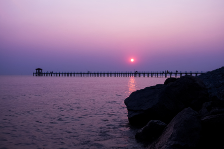Landscape,sea view Before sunset There is a bridge to the sea. There are people sitting in the natural view, purple sky. Imagens