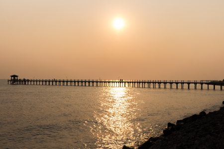Landscape,sea view Before sunset There is a bridge to the sea. There are people sitting in the natural view, Orange sky. Stock Photo