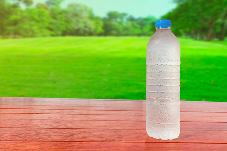 Cold water is placed on a beautifully colored wooden floor.with copy space On green grass field Background