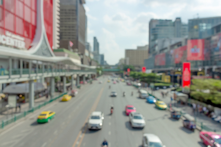 Sunny light shines over the buildings and car road of a busy Midtown in Bangkok street scene for blurry lens  - Image Stock Photo