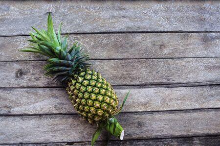 Frutta fresca verde dell'ananas su un vecchio fondo di legno con la luce della natura