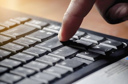 L'homme d'affaires appuie sur un bouton Entrée sur le clavier noir avec la lumière du soleil