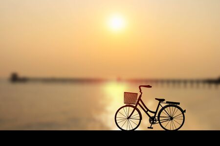 Silhouette womens style bike at sunset on seascape with bridge and cloud sky. Vector illustration design