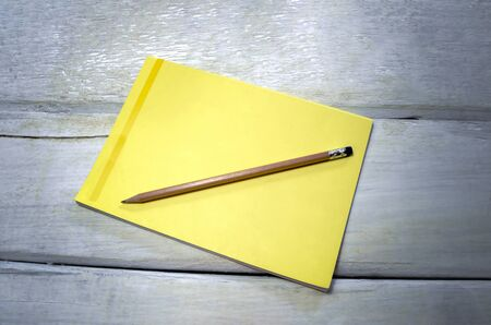 Concept of a pencil with a single black eraser Placed on a yellow note book and Placed on wood table vintage style