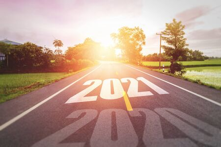 Concept new year With The word 2020 to 2021 Written on The asphalt  road in country road Decorate orange light for beauty Concept for new year of 2021 Stock Photo
